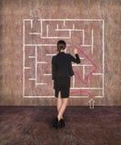 女实业家在墙壁上的图画迷宫 免版税库存照片