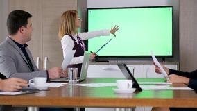 女实业家在大绿色屏幕电视前面的候选会议地点 影视素材