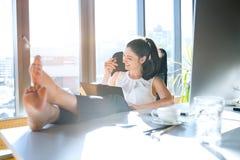 女实业家在她的办公室与腿坐书桌 库存图片