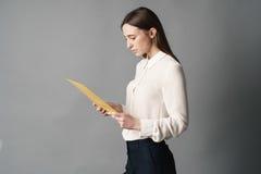 女实业家在她的手上拿着文件 一 查出在灰色背景 库存图片