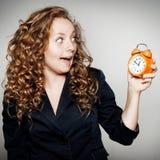女实业家在手上的拿着时钟 与shoc的最后期限概念 免版税库存图片