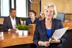 女实业家在招待会柜台的待办卷宗 免版税库存图片