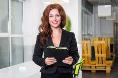 年轻女实业家在拿着有看照相机和微笑的任务名单的现代明亮的办公室片剂 事务co 库存图片