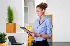 年轻女实业家在拿着有任务名单的现代明亮的办公室片剂 事务的企业概念 库存图片