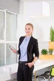 年轻女实业家在拿着有任务名单的现代明亮的办公室片剂 免版税库存照片