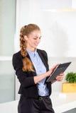 年轻女实业家在拿着有任务名单的现代明亮的办公室片剂 库存图片