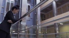 女实业家在旅馆里使用她的电话倾斜在栏杆 股票视频