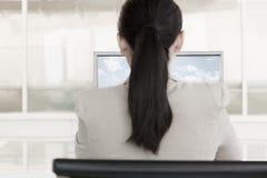 女实业家在有云彩和天空的一台计算机前面坐显示器 免版税库存照片