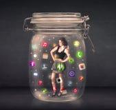 女实业家在有五颜六色的app象的c一个玻璃瓶子夺取了 免版税图库摄影