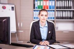 女实业家在有图的一个办公室在桌上 免版税库存照片
