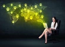 女实业家在有膝上型计算机和社会网络世界地图的办公室 免版税库存图片