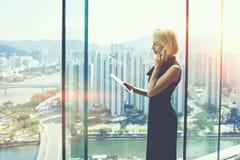 女实业家在现代办公室内部近的窗口里站立有都市风景视图 免版税库存照片