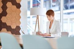 年轻女实业家在看她的电话的会议室里 免版税库存图片
