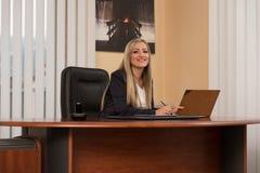 年轻女实业家在看纸的办公室 图库摄影