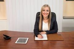 年轻女实业家在看纸的办公室 免版税库存照片