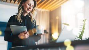 女实业家在计算机前面站立并且看屏幕,当喝咖啡,拿着数字式片剂时 女孩工作 库存图片
