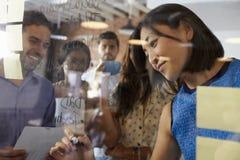 女实业家在玻璃屏幕上的文字想法在会议期间 免版税库存照片