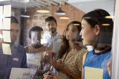 女实业家在玻璃屏幕上的文字想法在会议期间 免版税图库摄影