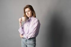 女实业家在他的手上站立并且拿着一个杯子 背景画笔关闭查出摄影白色的工作室牙 一在灰色背景 免版税库存照片