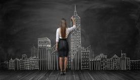 女实业家在黑背景的图画城市剪影后面看法  免版税库存图片