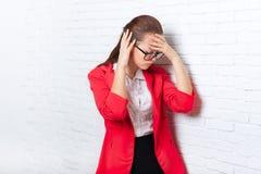 女实业家在头,疼痛的举行手,使沮丧的被注重的穿戴红色夹克玻璃痛苦 免版税库存图片