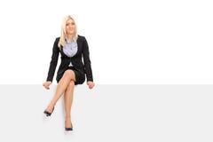 女实业家坐一个空白的广告牌 免版税库存图片