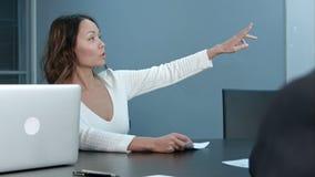 年轻女实业家坐与同事的业务会议在办公室,问问题 免版税库存图片