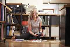 女实业家坐与数字式片剂的办公室地板 免版税库存照片
