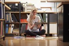 女实业家坐与数字式片剂的办公室地板 库存照片