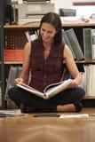 女实业家坐办公室地板读书文件 免版税库存照片