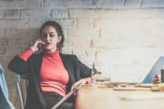 年轻女实业家坐在咖啡馆在桌上,倾斜对白色砖墙和谈话在手机 免版税图库摄影