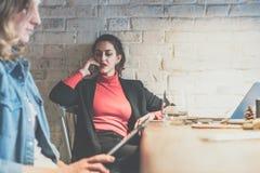 年轻女实业家坐在咖啡馆在桌上,倾斜对白色砖墙和谈话在手机 免版税库存图片