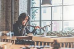 年轻女实业家坐在咖啡馆的桌上和谈话在手机 在桌上是膝上型计算机,咖啡,笔记本 库存照片