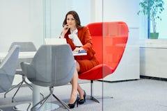 女实业家坐在玻璃办公室和工作的一把红色椅子 免版税库存照片
