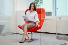 女实业家坐在玻璃办公室和检查文件的一把红色椅子 库存图片