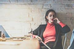 年轻女实业家坐在餐馆在桌上,倾斜对白色砖墙和谈话在手机 库存图片