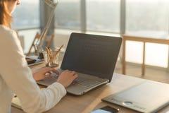 女实业家坐她的工作场所在办公室,键入,看个人计算机屏幕 免版税库存照片