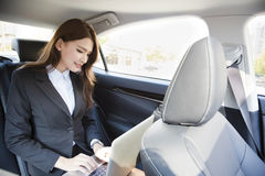 女实业家坐汽车位子和与膝上型计算机一起使用 免版税库存照片