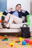 女实业家坐长沙发在杂乱室 库存图片