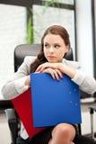 女实业家坐年轻人的椅子文件夹 免版税图库摄影