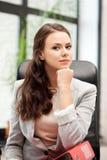 女实业家坐年轻人的椅子文件夹 库存照片