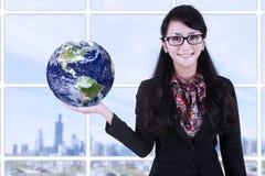 女实业家室内举行地球- 免版税库存图片