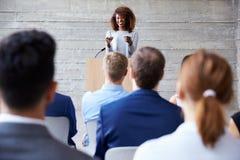 女实业家对代表演讲在会议 免版税库存图片