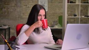 女实业家工作在膝上型计算机,饮料咖啡前面的办公室和同时观看屏幕 股票视频