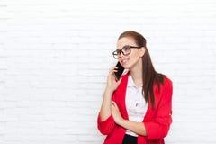 女实业家愉快的微笑手机电话穿戴红色夹克玻璃谈话在机动性 免版税库存图片