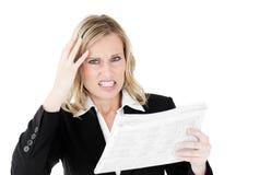 女实业家愤怒的查找的报纸 免版税库存图片