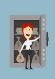 女实业家打开有金钱的一个保险柜 库存照片
