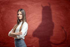 年轻女实业家投下恶魔的阴影在生锈的橙色墙壁上的在她后 图库摄影