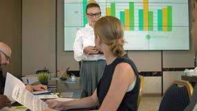 女实业家报告人在白色屏幕附近的业务会议有图表和观众的 股票录像