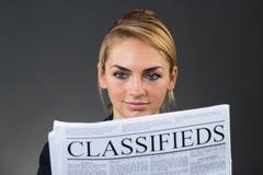 女实业家报纸读取微笑 库存照片